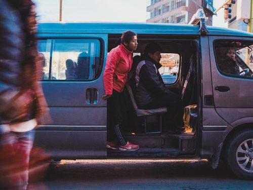 Kobieta wysiadające z busa w różowej kurtce