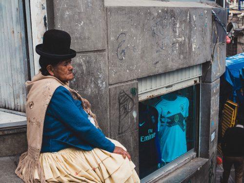 Kobieta w niebieskim swetrze i czarnym kapeluszu siedzi na ulicy