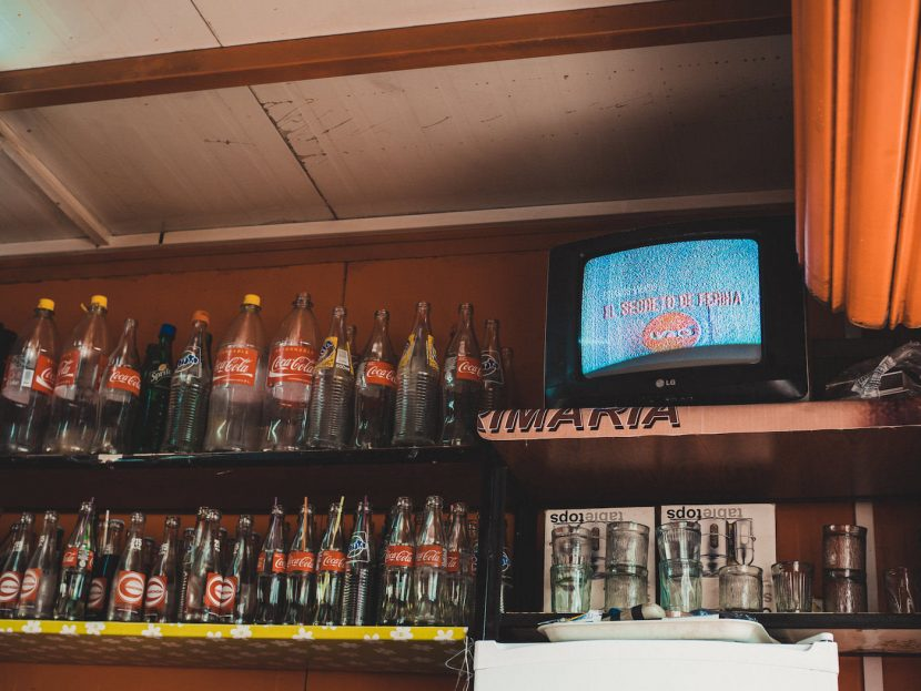 Coca cola na półkach w barze i telewizor