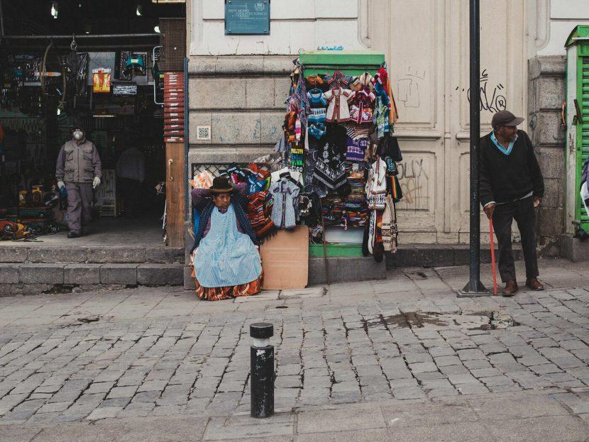 Kobieta na ulicznym stoisku i mężczyzna opierający się o latarnię