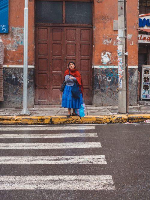KObieta w niebieskiej sukience i czerwonym szaliku na przejściu dla pieszych