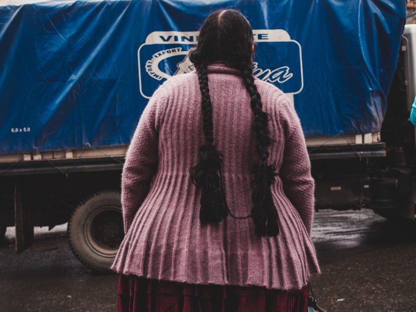 Kobieta w różowym swetrze z długimi warkoczami na tle niebieskiej ciężarówki