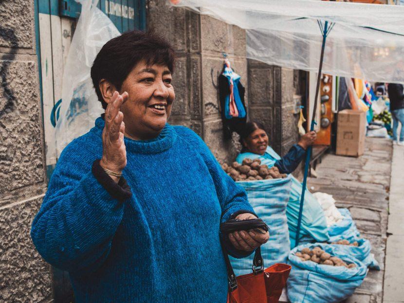 Kobieta na stoisku z ziemniakami w niebieskim swetrze