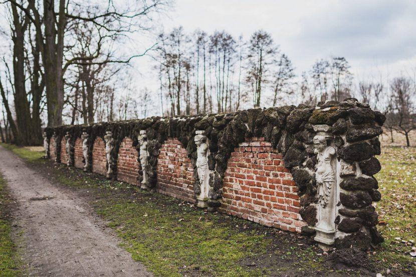 ceglany mur i posągi