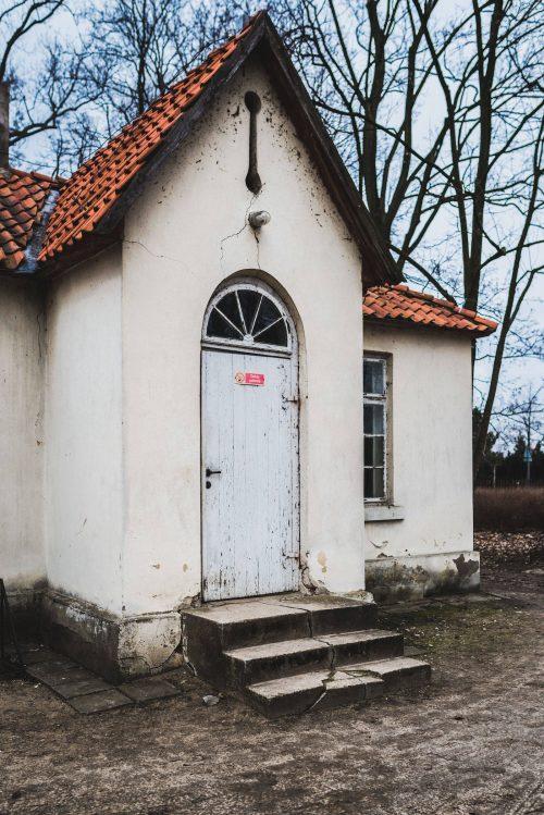 drzwi do białego budynku w parku