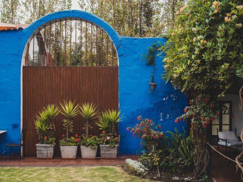 Niebieska brama zastawiona kwiatami