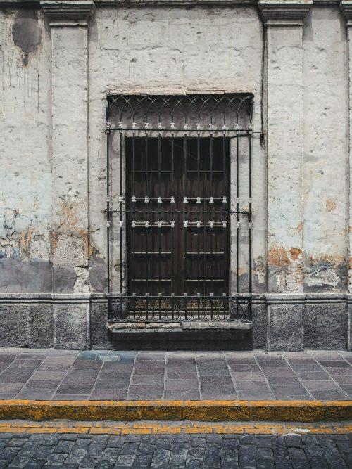 Czarne drzwi zasłoniete kratą