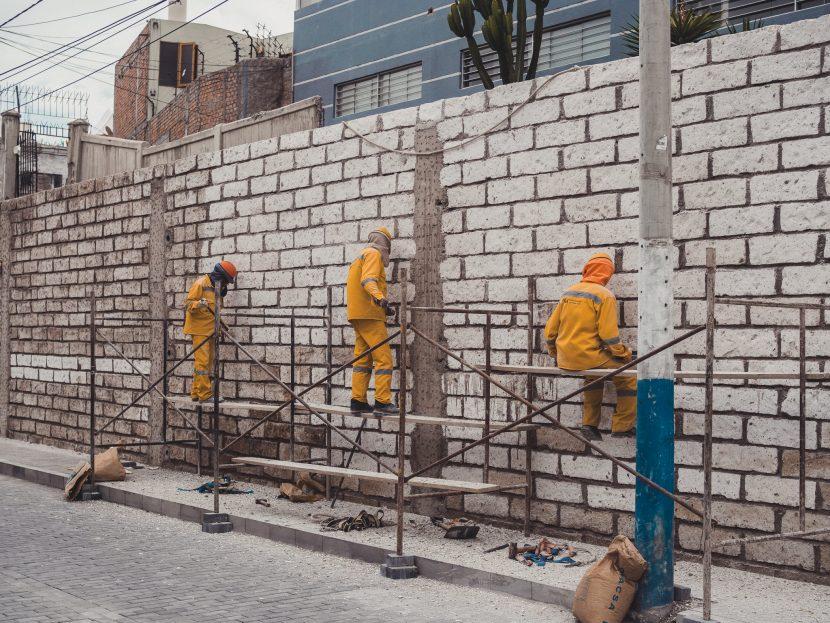Robotnicy w pomarańczowych strojach myją mur