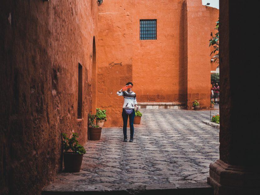 Dziewczyna z telefonem na tle pomarańczowej ściany
