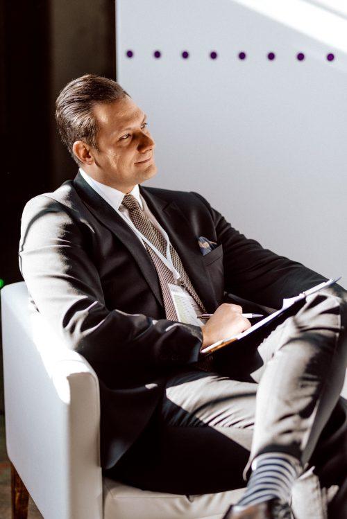 Prowadzący na fotelu z długopisem w ręku