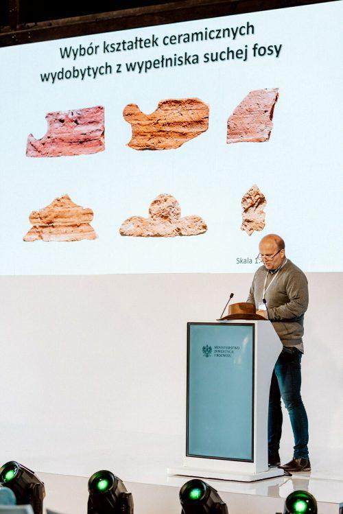 Mężczyzna mówi o odkryciach archeologicznych na scenie