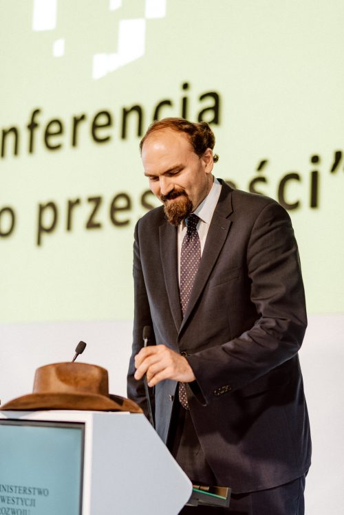 Mężczyzna poprawia mikrofon na mównicy