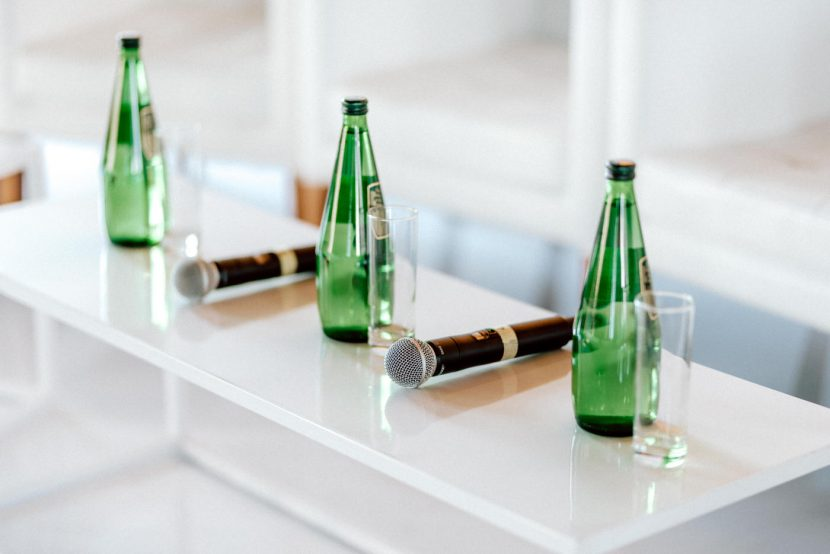 Water bottles and microphones on white tables