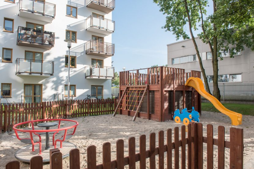 A photo of a playground in a backyard in Warsaw