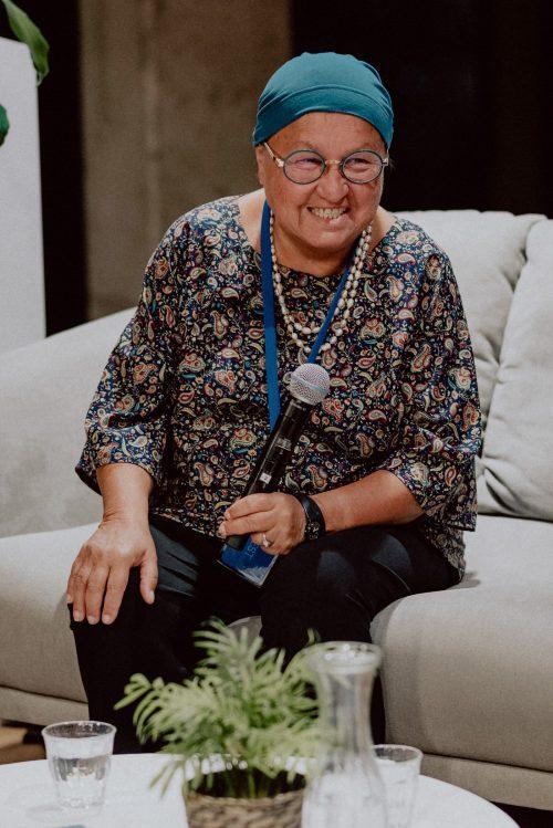 Roześmiana kobieta na kanapie z mikrofonem w ręku