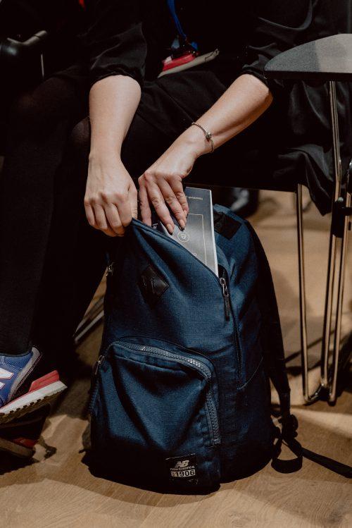 Dłonie chowające magazyn do plecaka