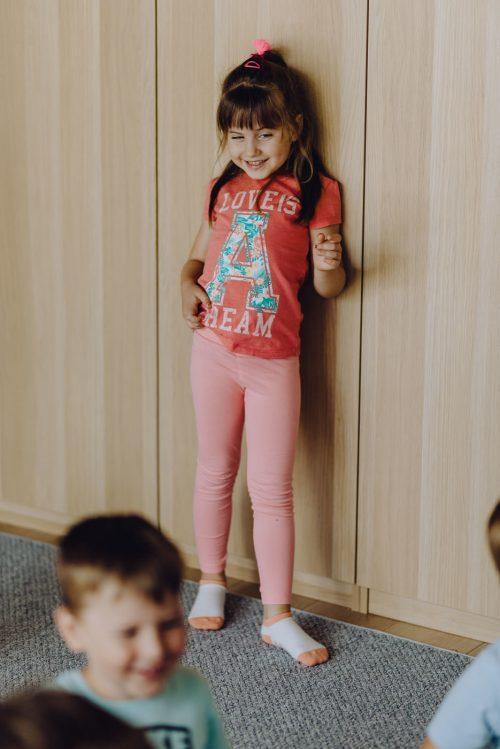 Uśmiechnięta dziewczynka opiera się o szafę