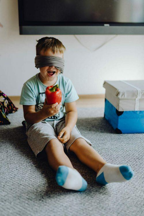Chłopiec trzyma paprykę w dłoni i się cieszy