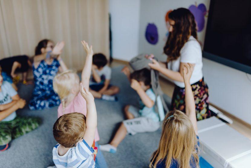 Dzieci podnoszą ręce podczas zajęc
