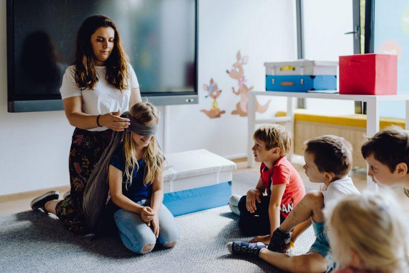 Nauczycielka zawiązuje dziewczynce oczy opaska podczas zabawy