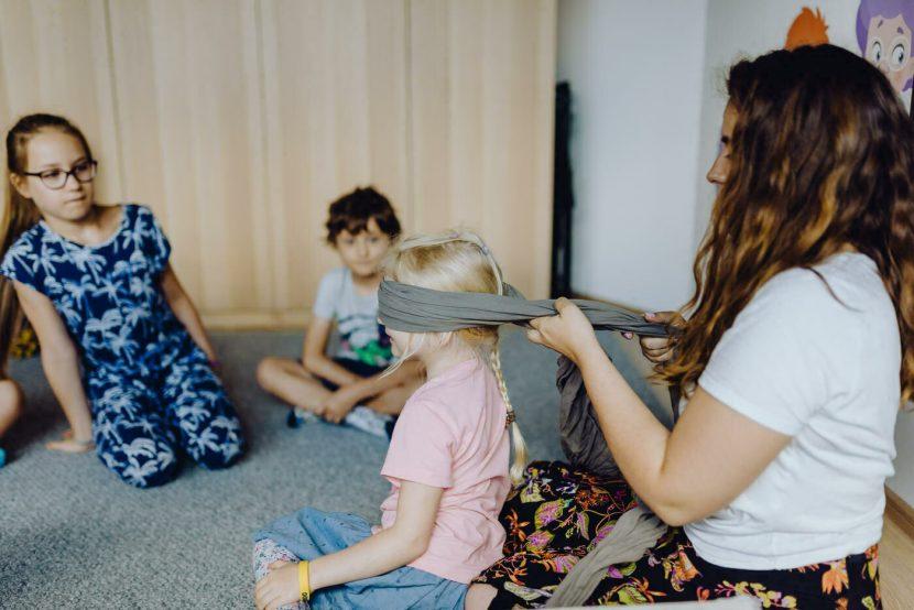 Nauczycielka zawiązuje dziewczynce oczy
