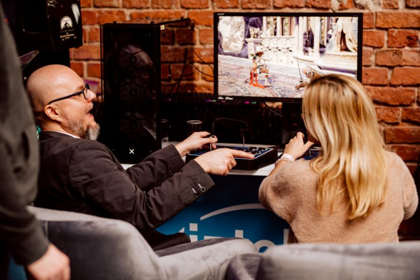 The man is playing retro fighting game with a woman