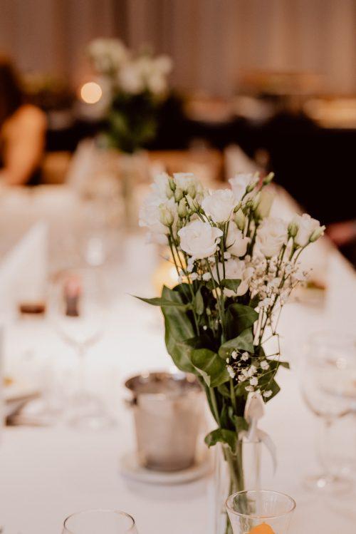 Białe róże na stole w hotelu