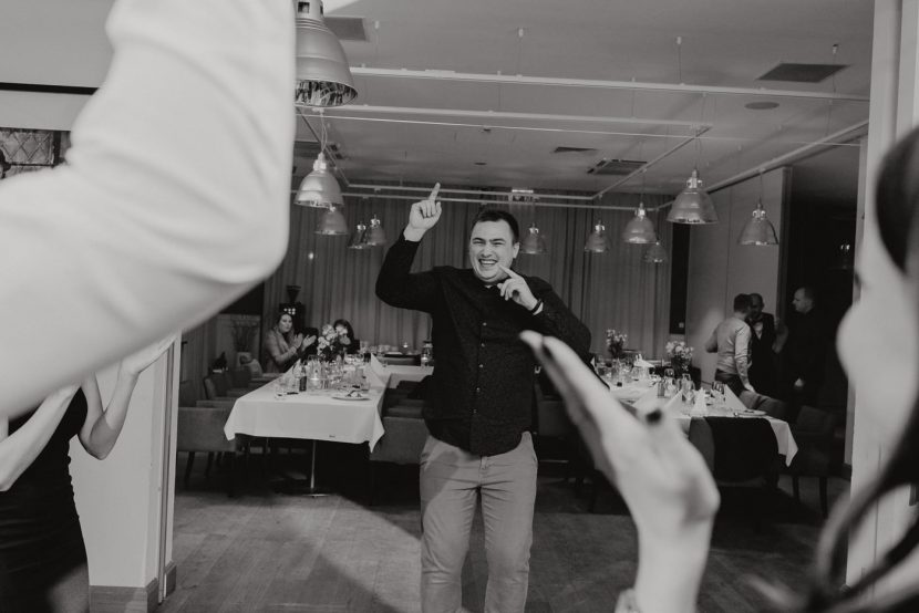 The man jumping the tables behind him on the dance floor