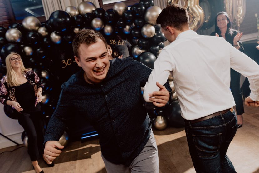 The men are dancing in circles on the dance floor