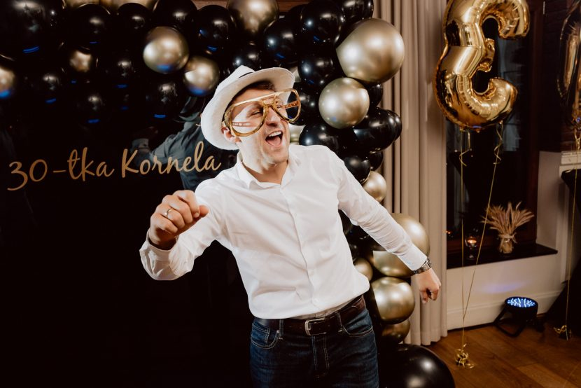 The man in the white shirt, white hat and golden glasses is dancing