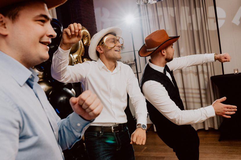 Men on the dance floor in cowboy hats