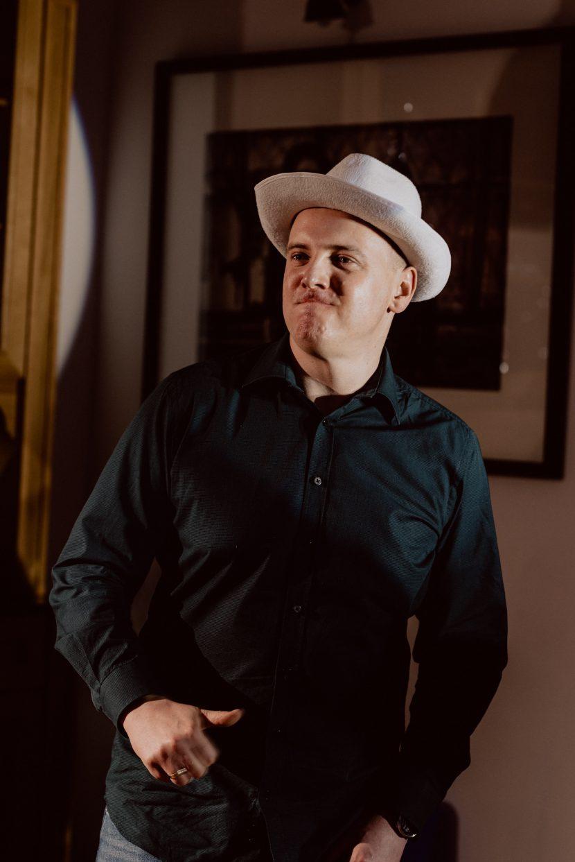 Mężczyzna w białym kapeluszu i czarnej koszuli tańczy