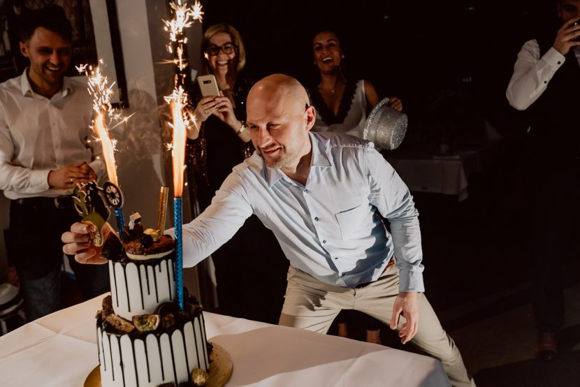 A man in a blue shirt corrects the birthday cake