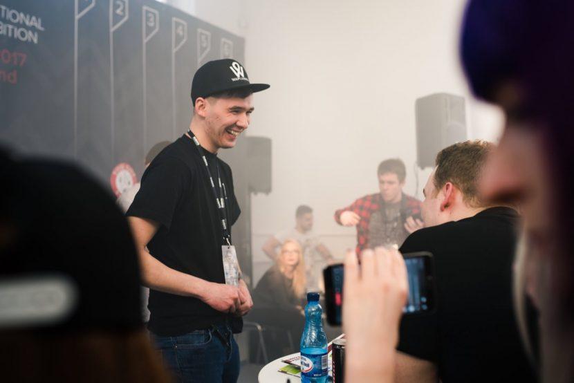 chłopak na scenie w czarnej czapce i koszulce
