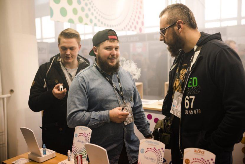chłopak z brodą pali e-papierosach na targach vape expo na mińskiej