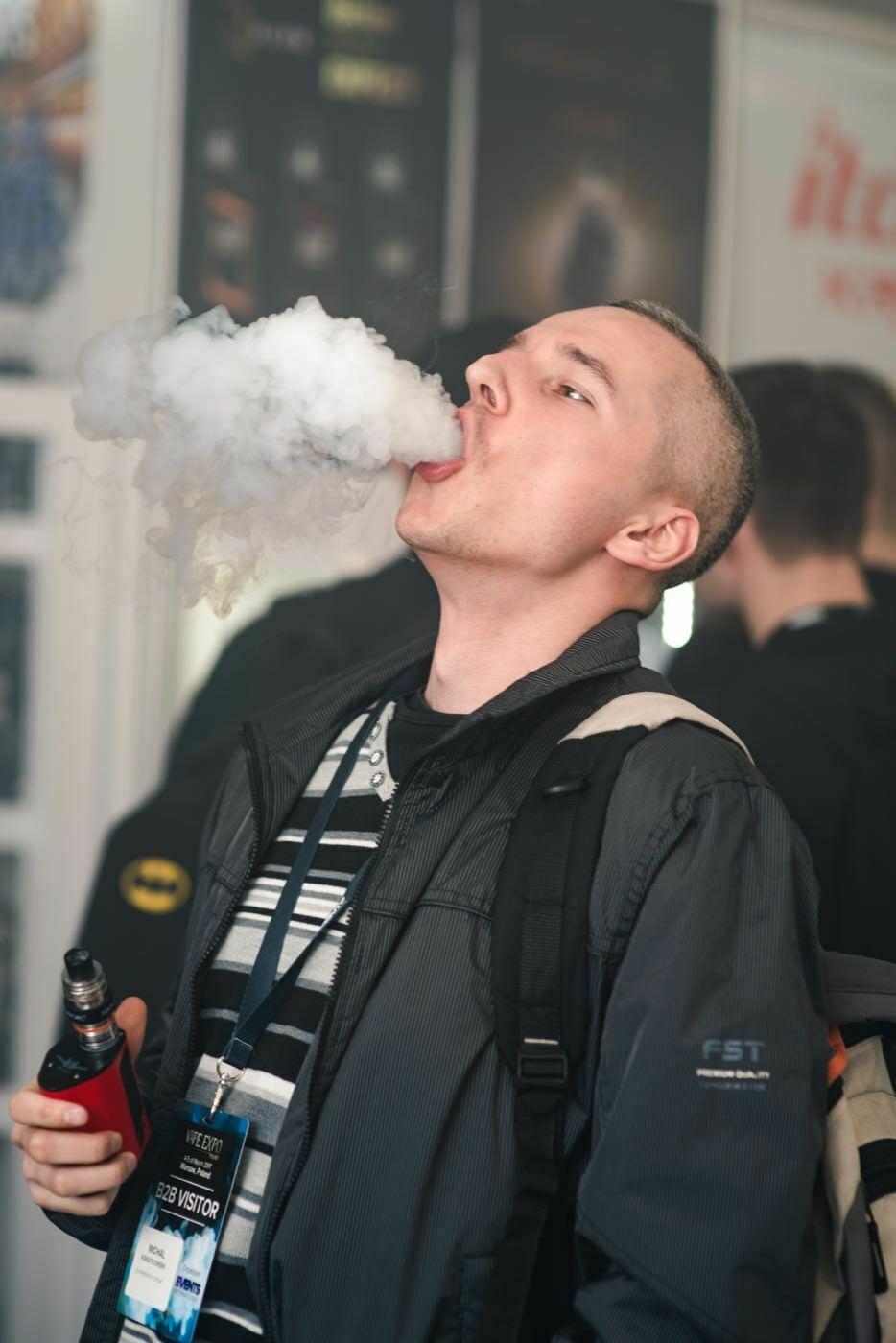 chłopak wypuszcza chmurę dymu paląc e-papierosa