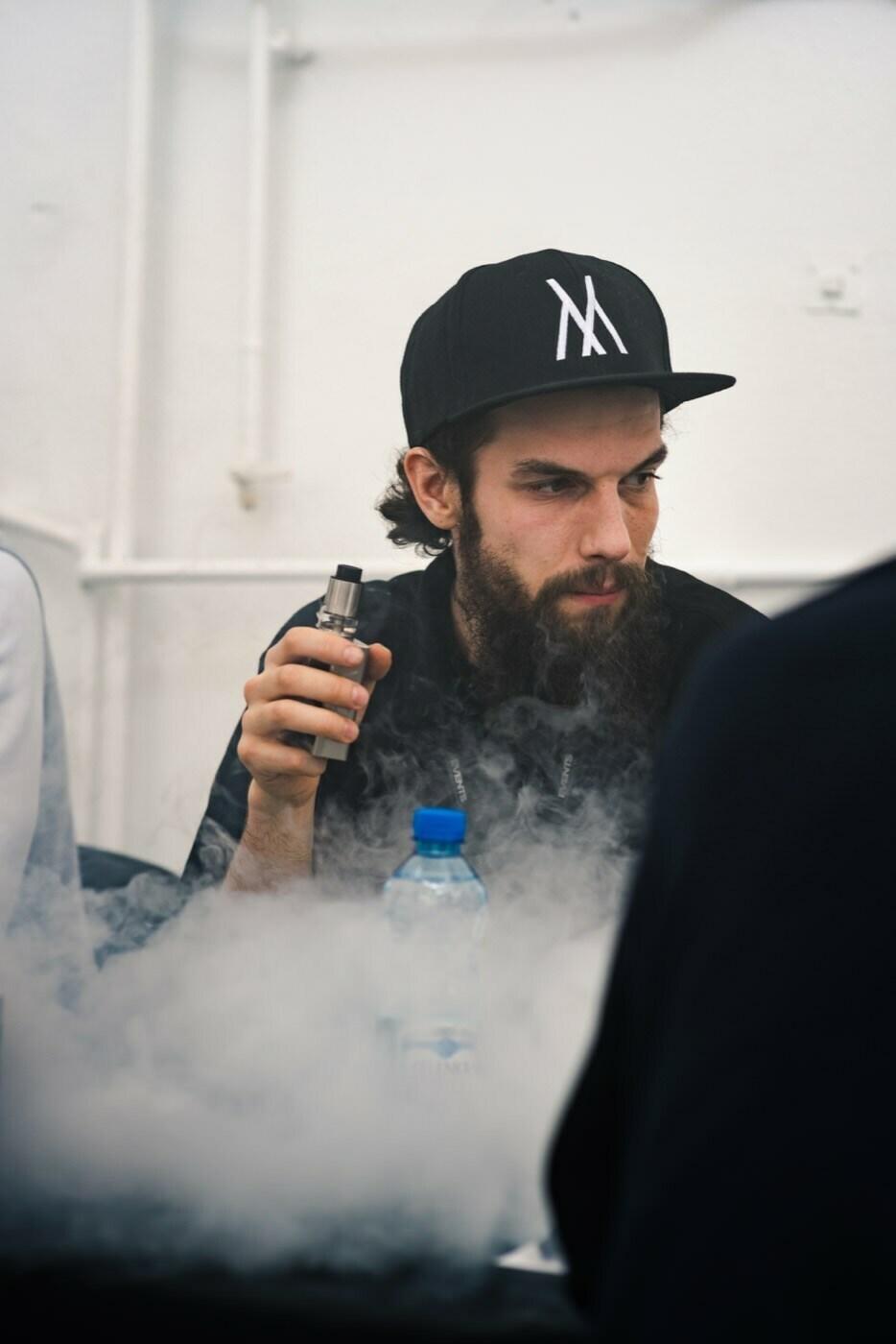 mężczyzna w czarnej czapce pali e-papieros