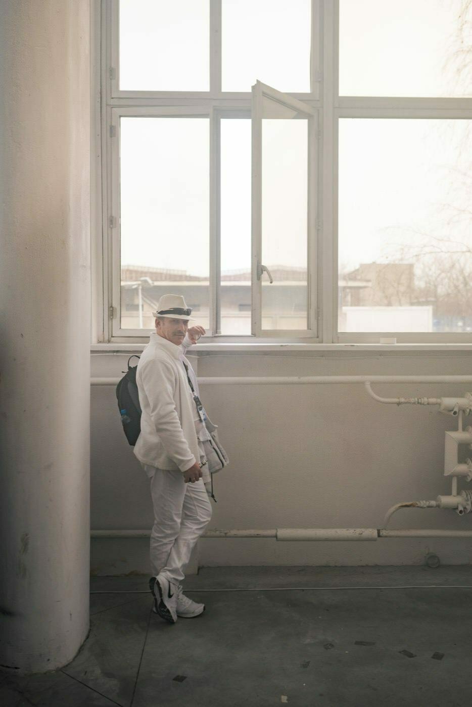Męzcvzyzna w białych ubraniach i kapeluszu stoi przy oknie