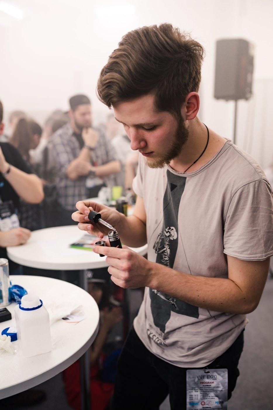 Chłopak uzpełnia swój e-papieros