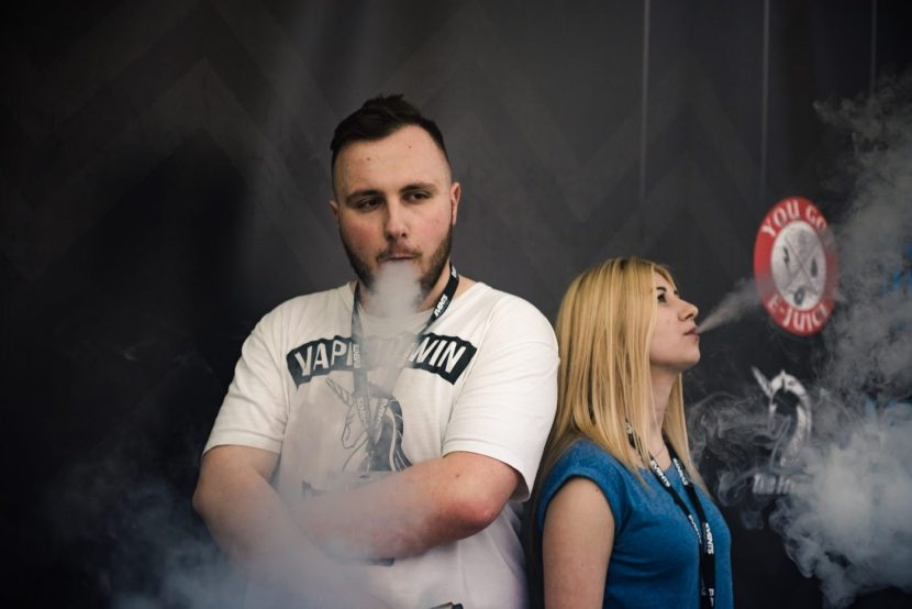 girl and boy blowing e-cigarette smoke