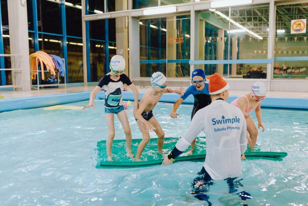 Dzieci próbujące utrzymać równowagę na piątkowej tratwie pod okien instruktora Swimple