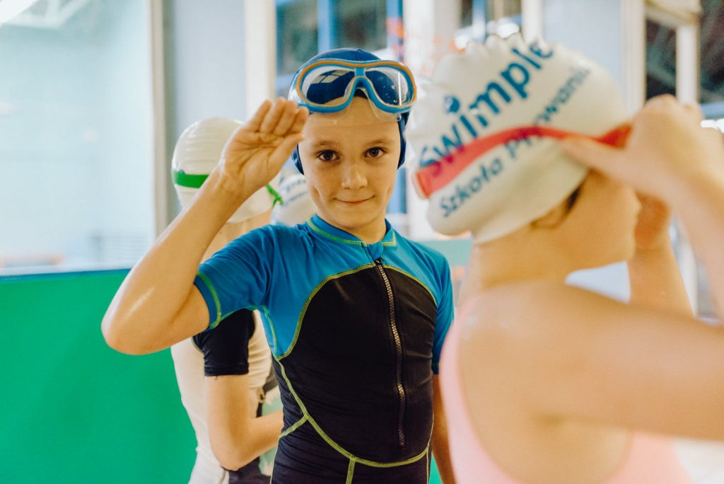 Chłopiec w stroju kąpielowym i okularach do nurkowania salutuje