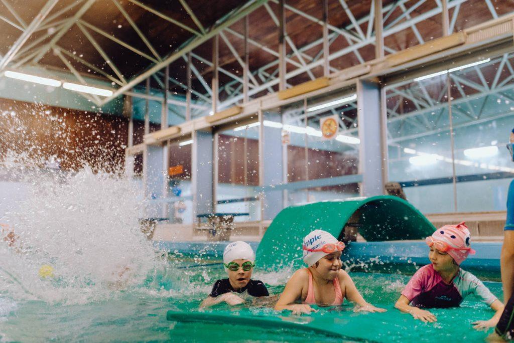 Dzieci skaczące do wody na basenie