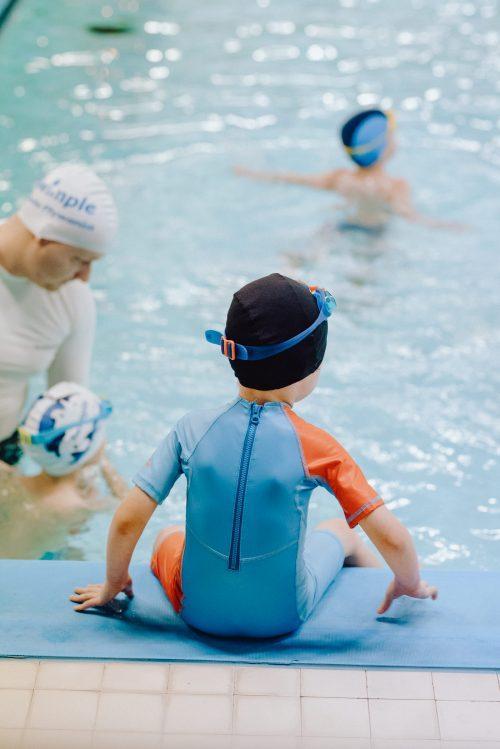 Chłopiec na brzegu basenu w niebieskim stroju