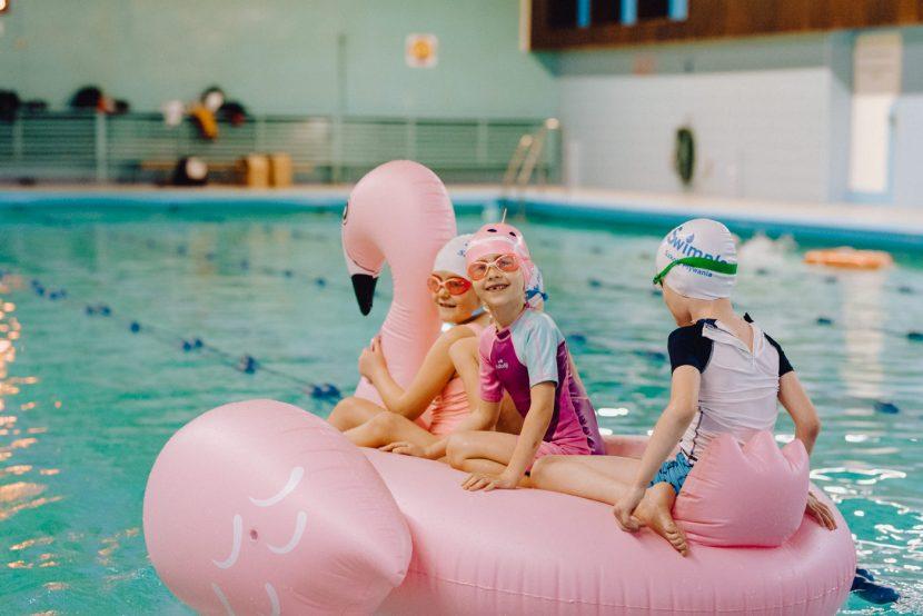 Dzieci na basenie pływają na dmuchanym flamingu