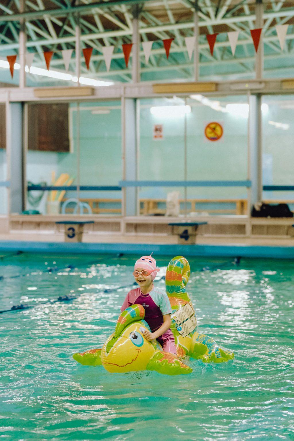 Dziewczynka pływa na dmuchanej jaszczurce