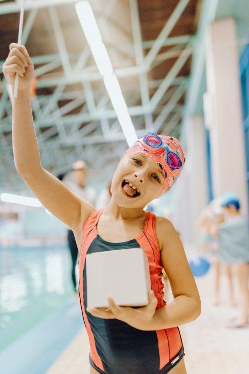 Dziecko pokazuje język na basenie