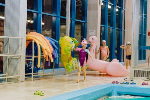 Dzieci z dmuchanymi zabawkami na basenie