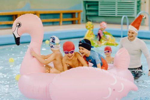Dzieci bawią się dmuchanym flamingu