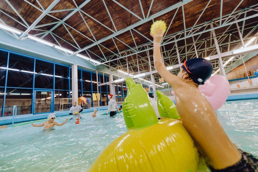 Chłopiec rzuca żółta piłką na basenie
